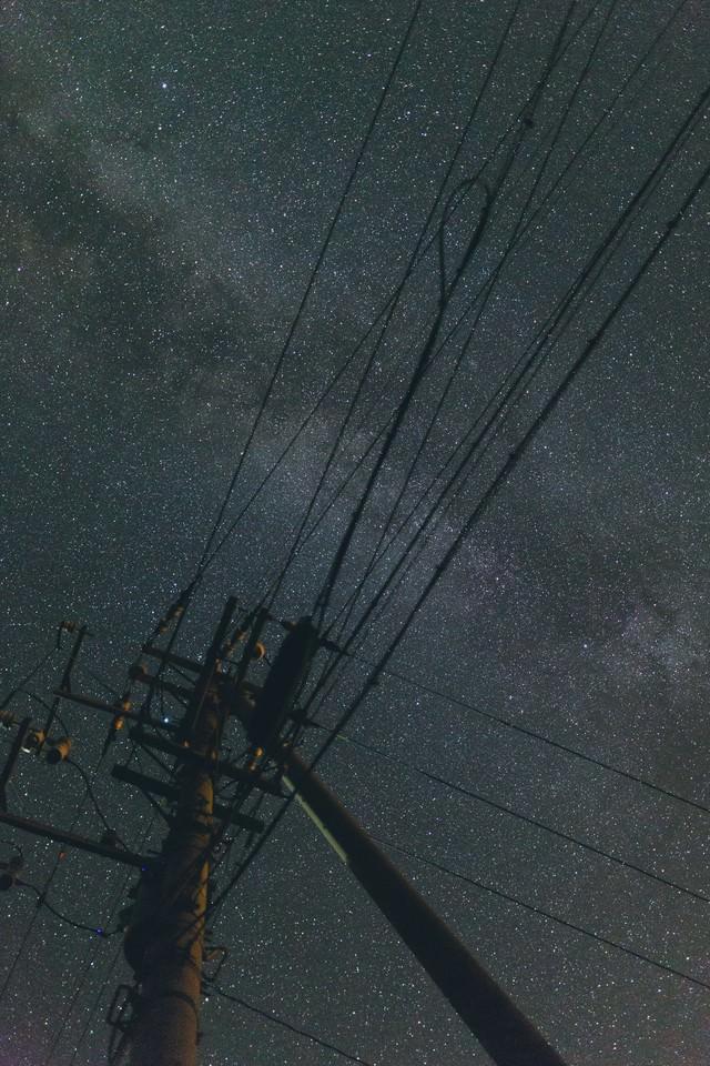 電柱のシルエットと輝く星空の写真