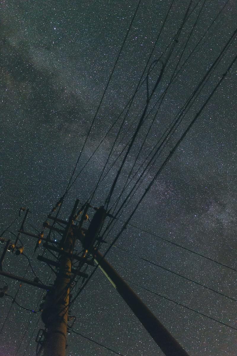 「電柱のシルエットと輝く星空」の写真