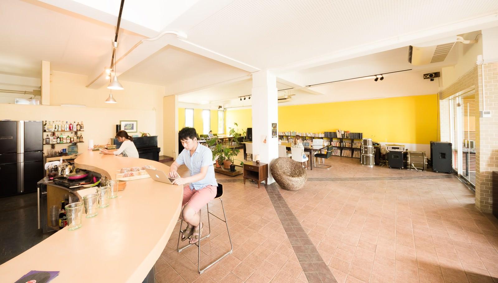 「コワーキングカフェのカウンターで作業をする男性」の写真[モデル:大川竜弥]