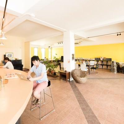 コワーキングカフェのカウンターで作業をする男性の写真