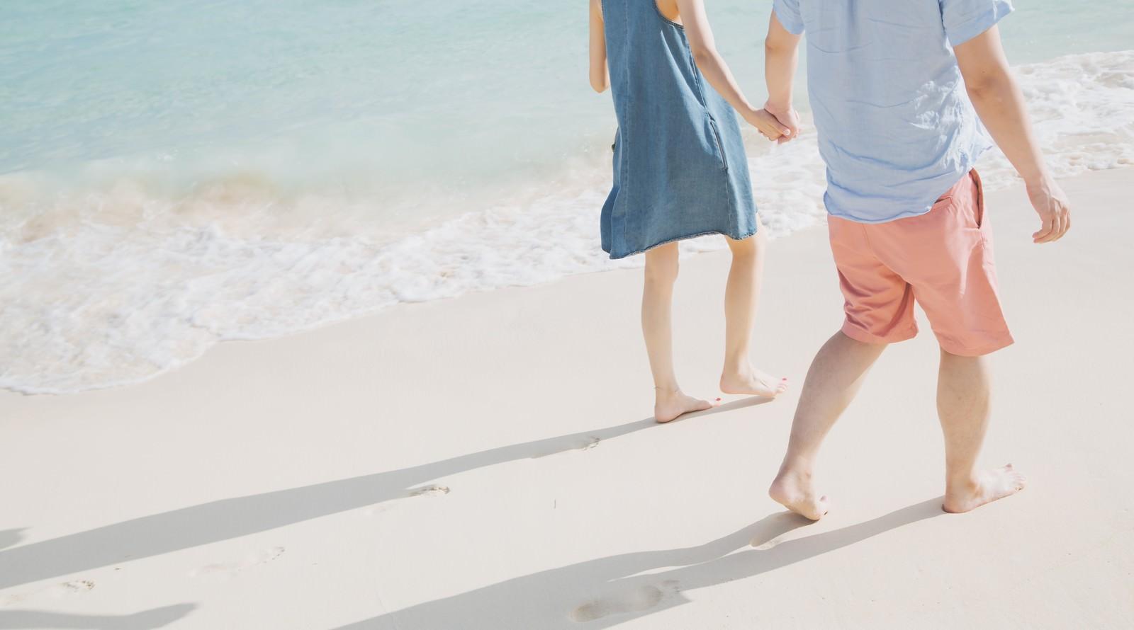 「波打ち際を歩く恋人と足あと」の写真