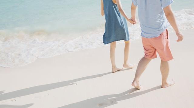波打ち際を歩く恋人と足あとの写真