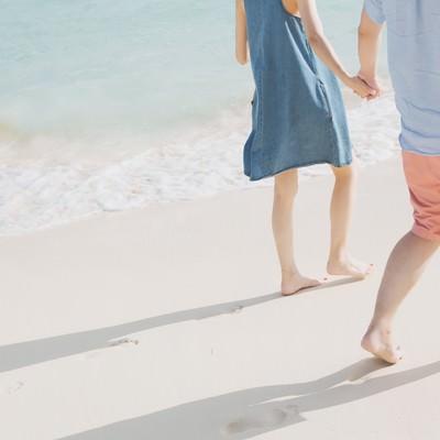 「波打ち際を歩く恋人と足あと」の写真素材