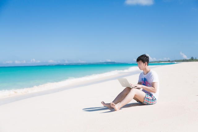 海で楽しそうに泳ぐ同僚を見ながら、ひざの上にMacBook Airを乗せて改修案件をするエンジニアの写真
