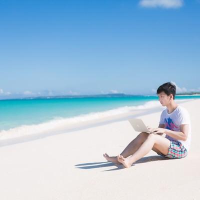 「海で楽しそうに泳ぐ同僚を見ながら、ひざの上にMacBook Airを乗せて改修案件をするエンジニア」の写真素材