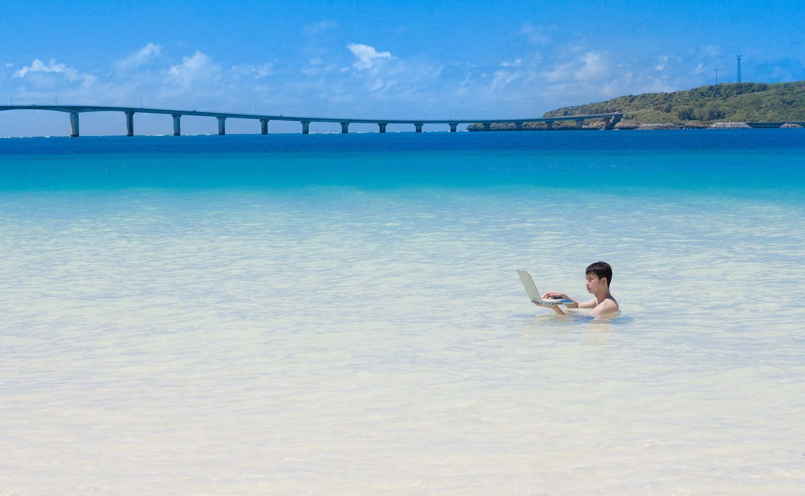 「来間島をバックに、海水浴中も即座にメールの返信をする意識高いIT戦士」の写真[モデル:大川竜弥]