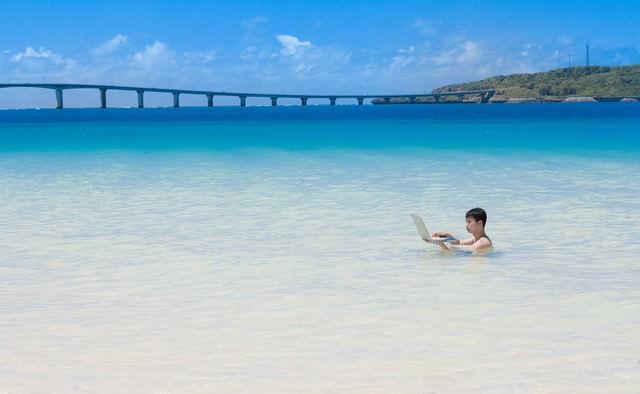 来間島をバックに、海水浴中も即座にメールの返信をする意識高いIT戦士の写真