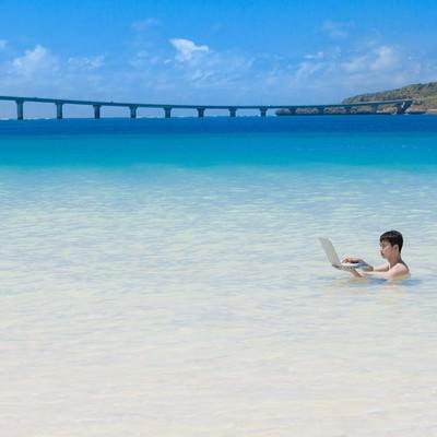 「来間島をバックに、海水浴中も即座にメールの返信をする意識高いIT戦士」の写真素材