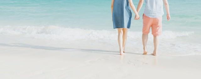 波打ち際で手を握るカップルの写真