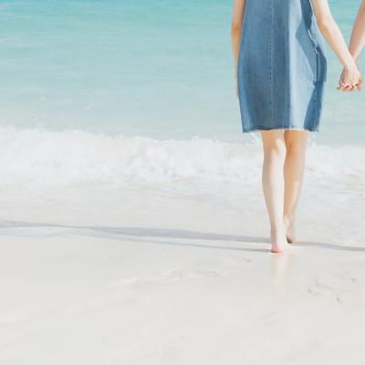 「波打ち際で手を握るカップル」の写真素材