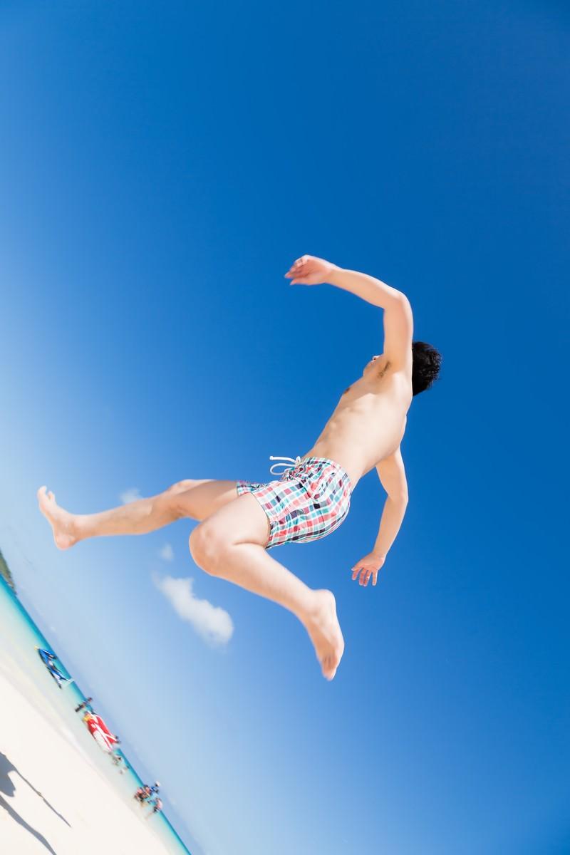 「透き通る海、晴れ渡る空、駆け出す男性」の写真[モデル:大川竜弥]