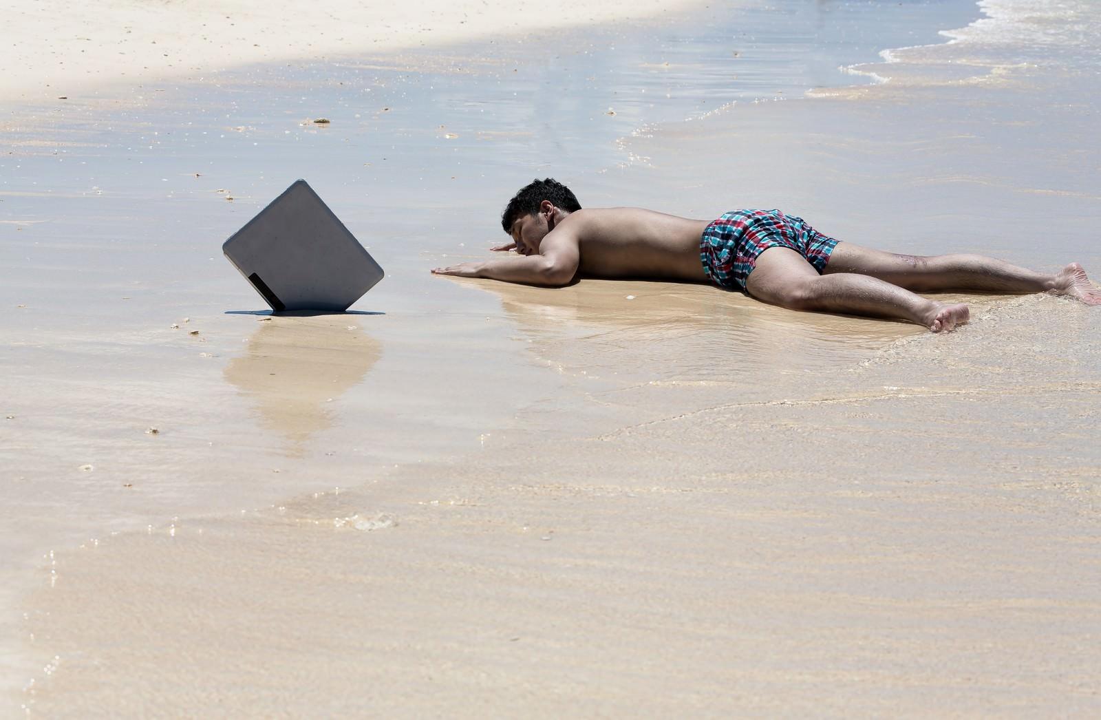 「納期に追われ一週間ほど漂流した後、砂浜に打ち上げられたノマドワーカー」の写真[モデル:大川竜弥]
