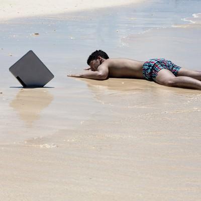 「納期に追われ一週間ほど漂流した後、砂浜に打ち上げられたノマドワーカー」の写真素材