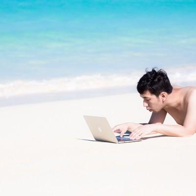 「宮古島の前浜ビーチで急な修正依頼に対応するバカンス中のプログラマー」の写真素材