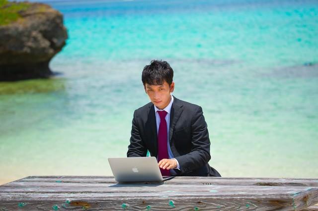 リゾート地でスーツ姿で仕事する男性の写真