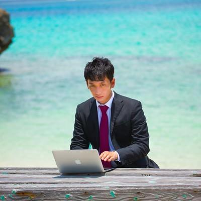 「リゾート地でスーツ姿で仕事する男性」の写真素材