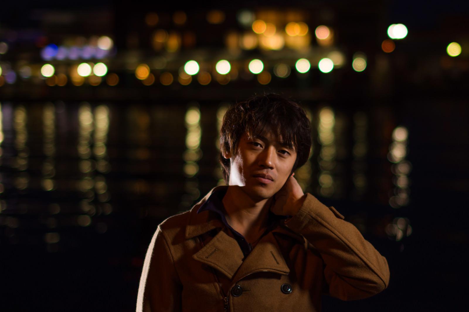 「夜景と首を痛めた男子」の写真[モデル:Tsuyoshi.]
