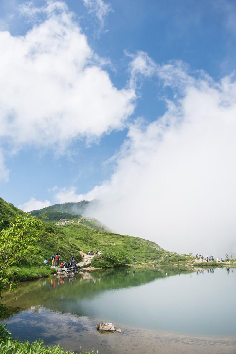 「湖面に映る雲と登山者」の写真