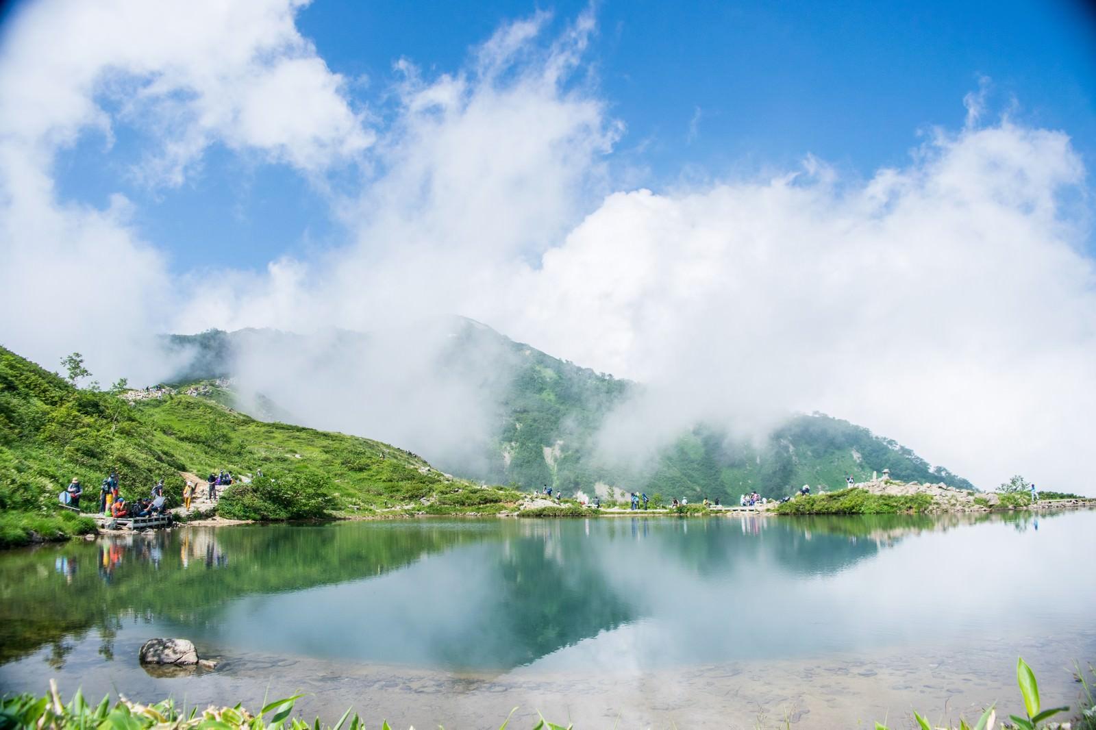 「湖面に映り込む雲と休憩中の登山者」の写真