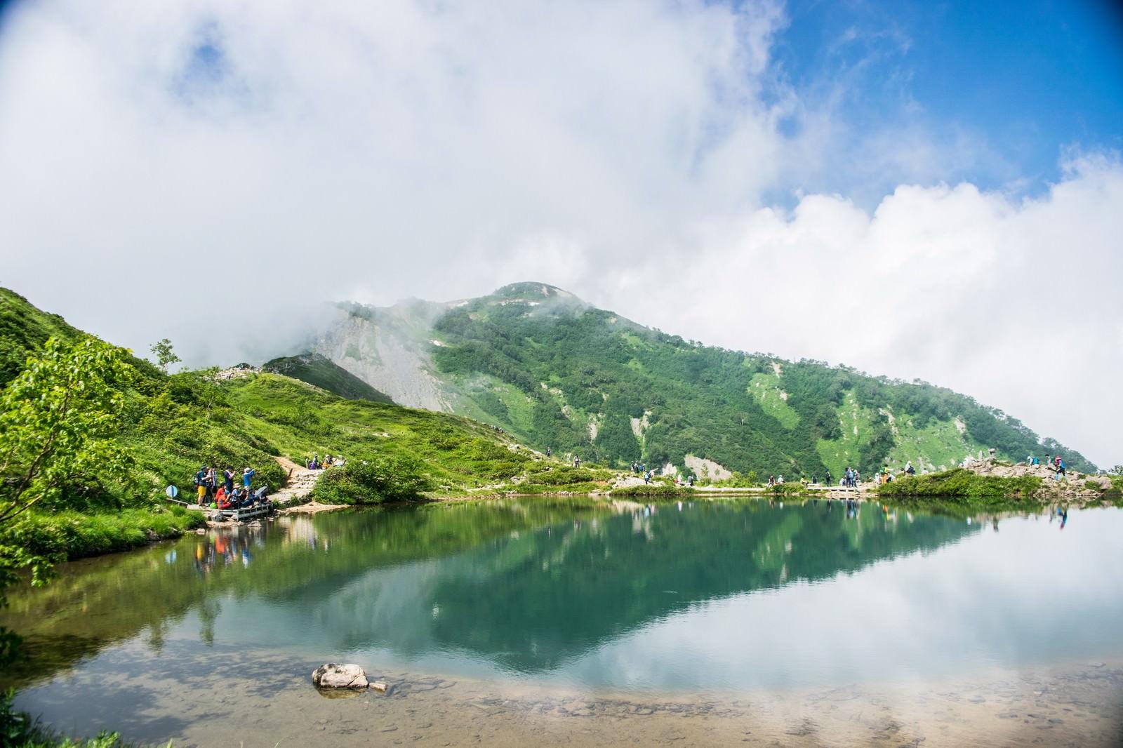 「湖の周りでカメラを構える登山者達」の写真