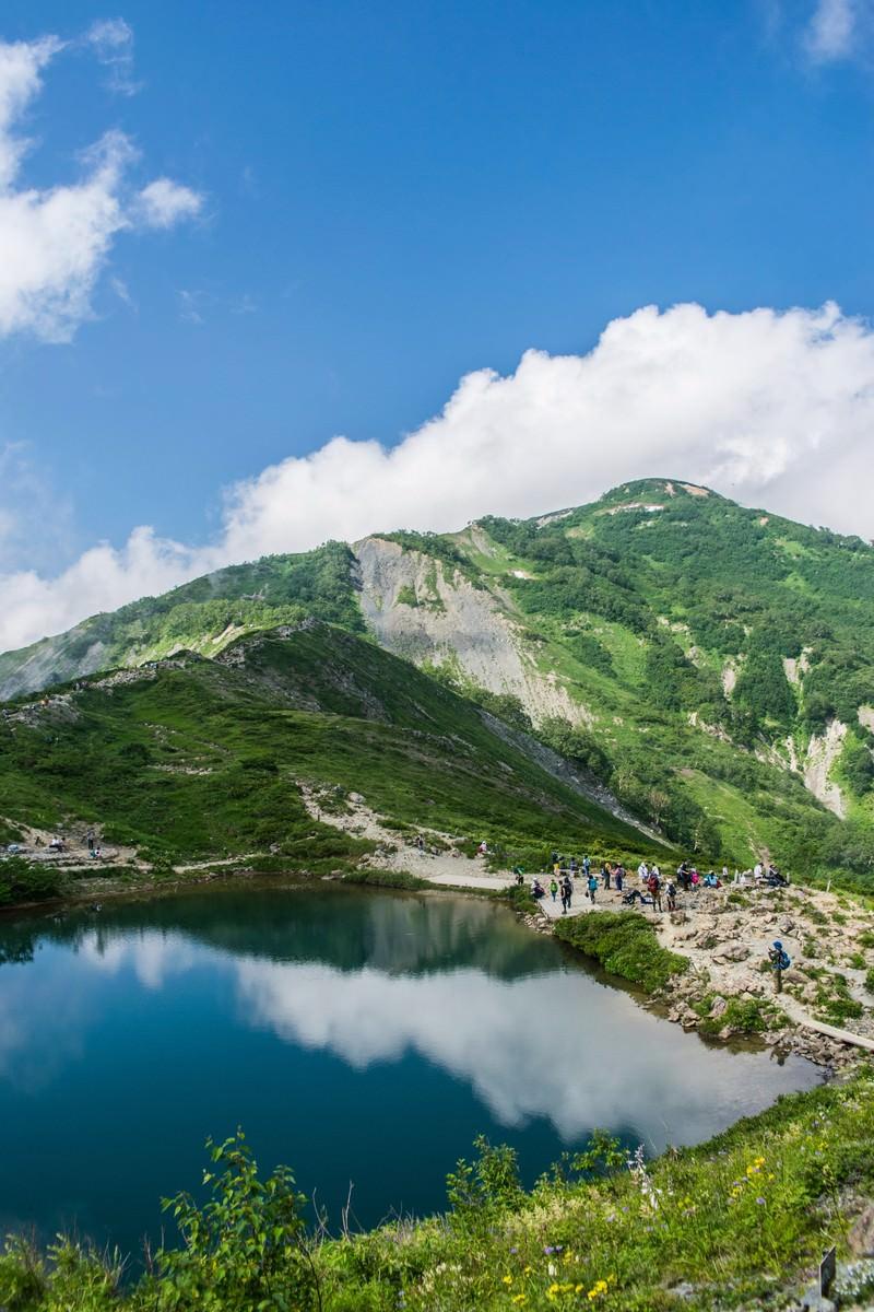 「湖畔に映る景色と登山者」の写真