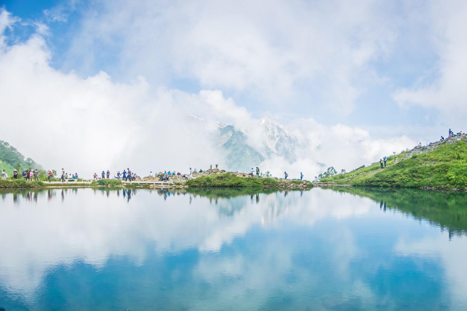 「沸き立つ雲のリフレクションと登山者の列」の写真