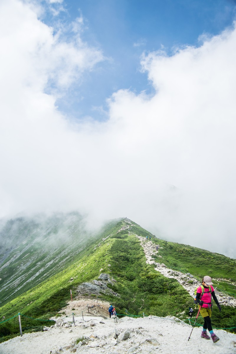 「雲の中の尾根を進む登山者」の写真
