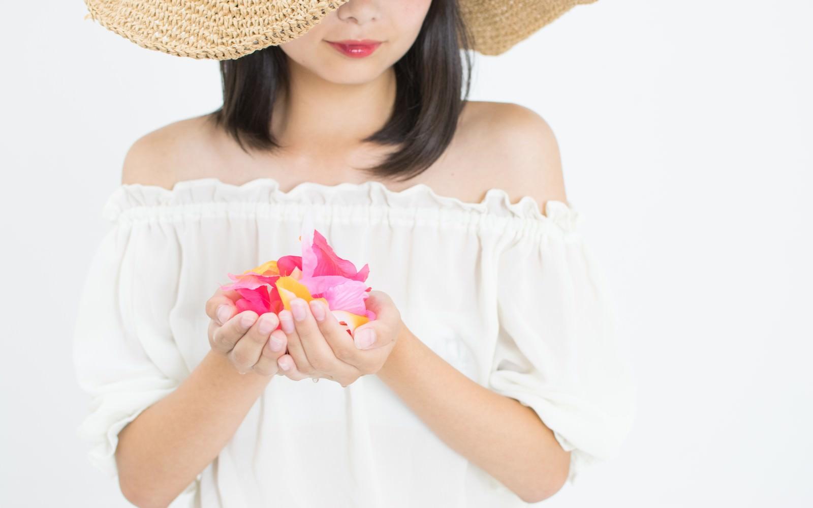 「彩る花を手に抱える女性」の写真