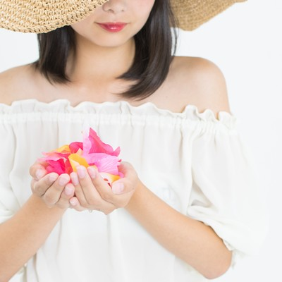 「彩る花を手に抱える女性」の写真素材