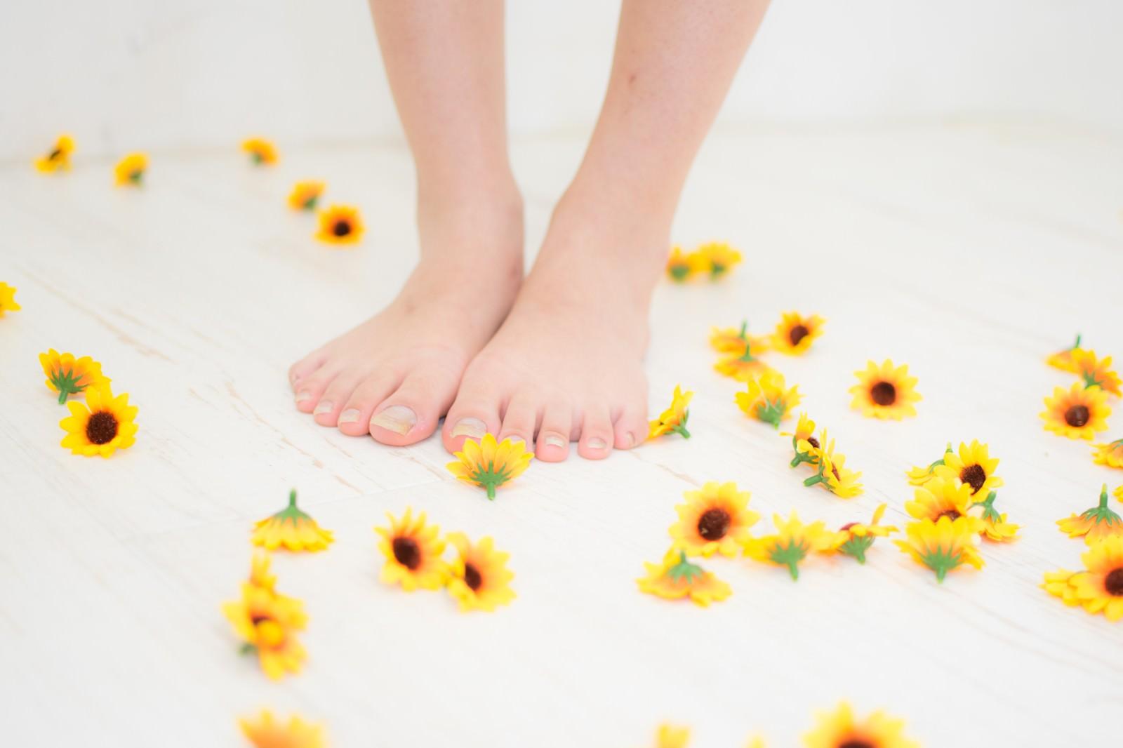 「床に散らばる小さいひまわりのブローチと足元」の写真