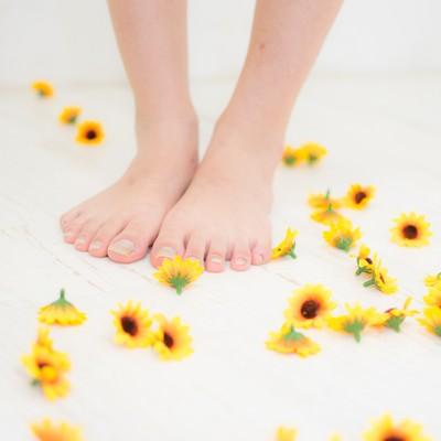 床に散らばる小さいひまわりのブローチと足元の写真