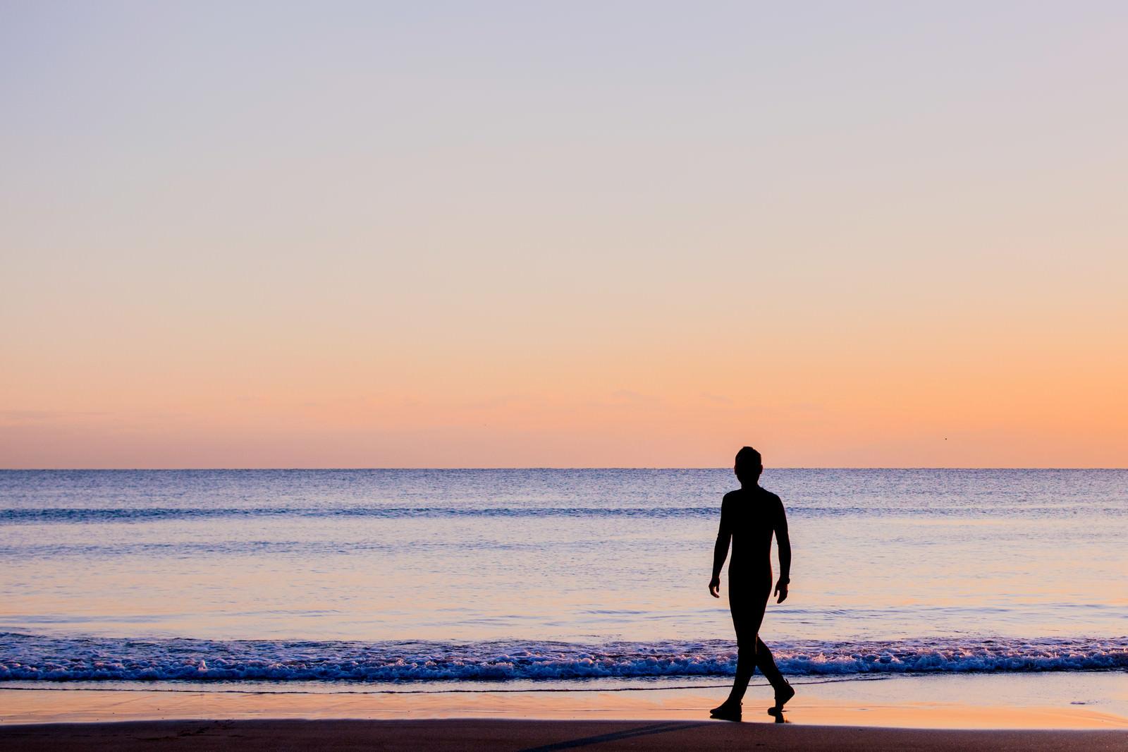 「夕暮れの砂浜を歩く男性のシルエット」の写真