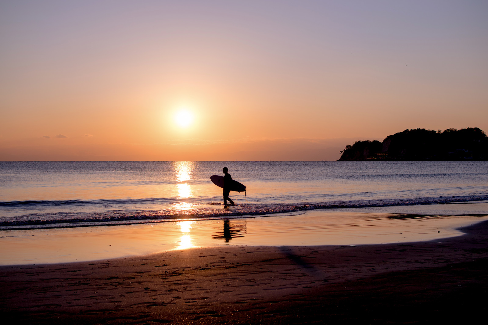 「夕暮れの海に向かうサーファー」