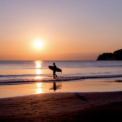 夕暮れの海に向かうサーファーの写真