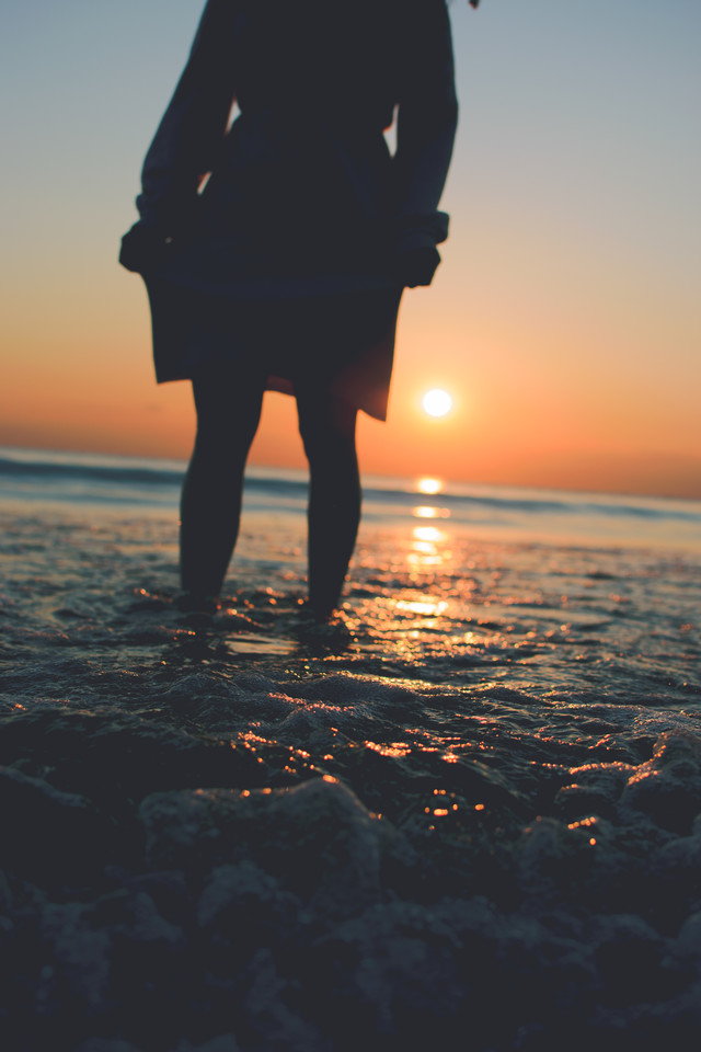 夕日を見る女性と崩れて泡立つ波の写真