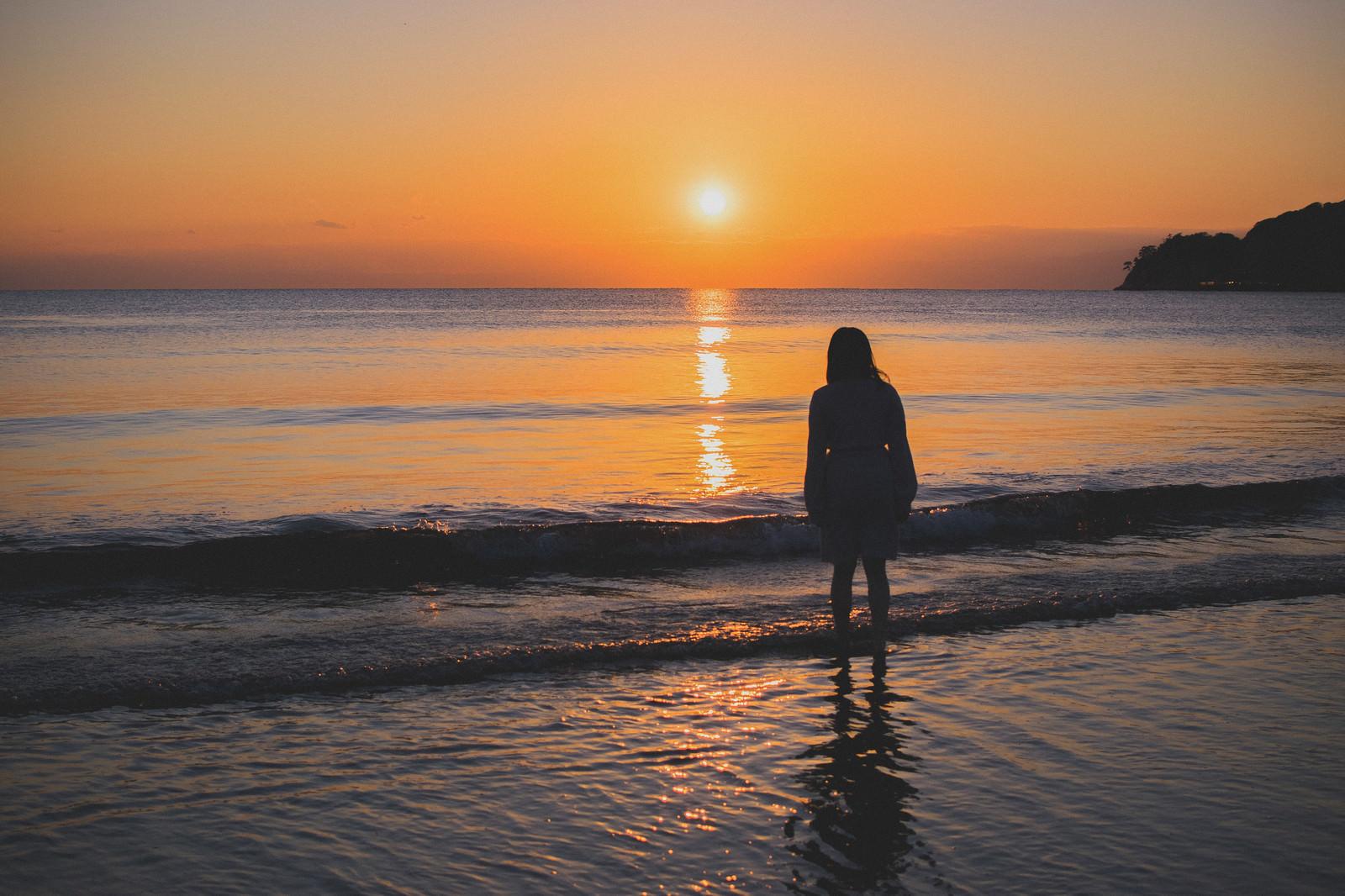 「夕日に向かって浜辺に立ちすくむ女性」の写真