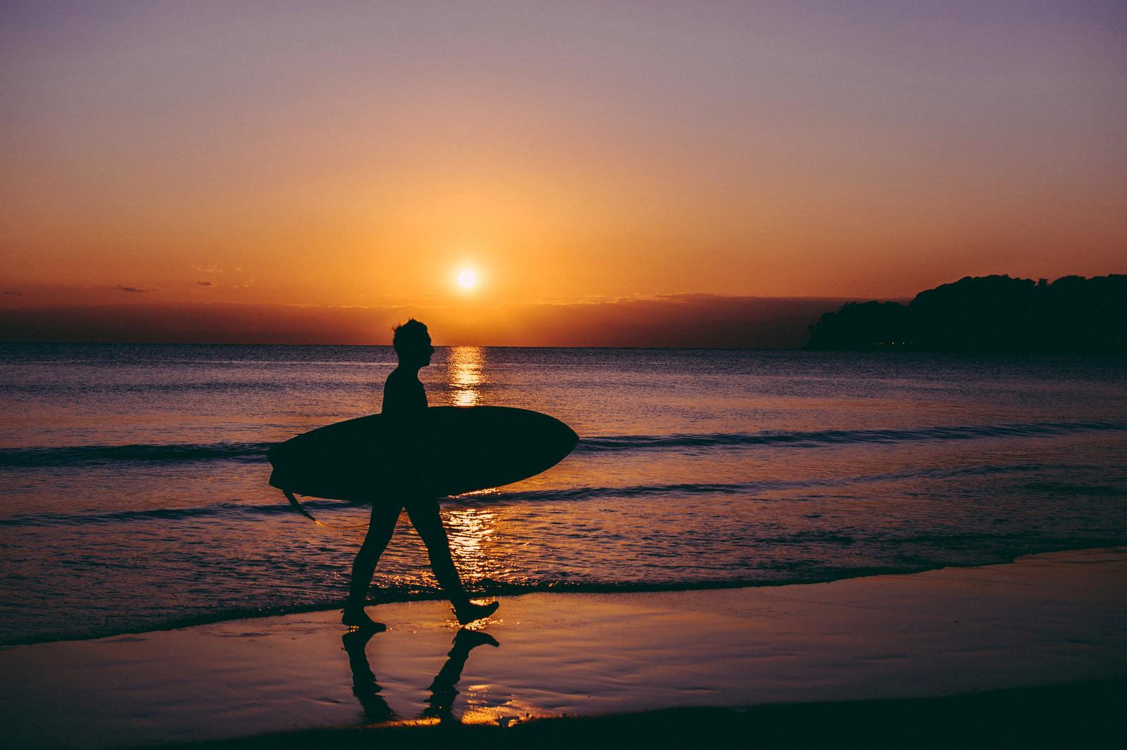 「夕暮れとともに海から上がるサーファー」の写真