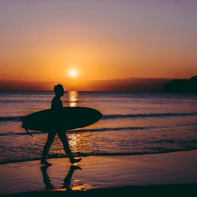 夕暮れとともに海から上がるサーファーの写真