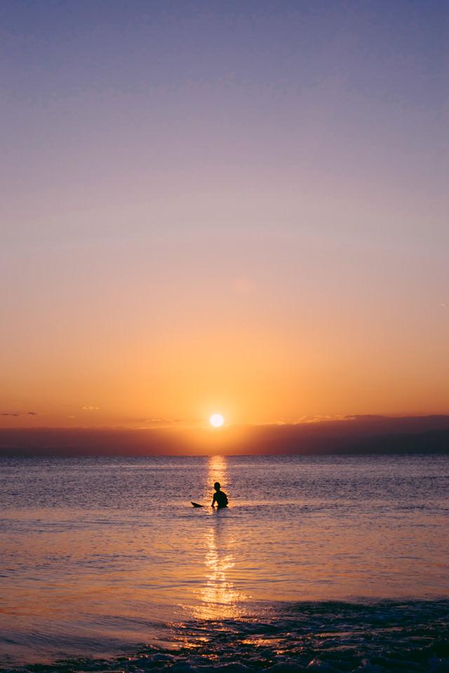 夕暮れのレイラインで波待ちするサーファーの写真