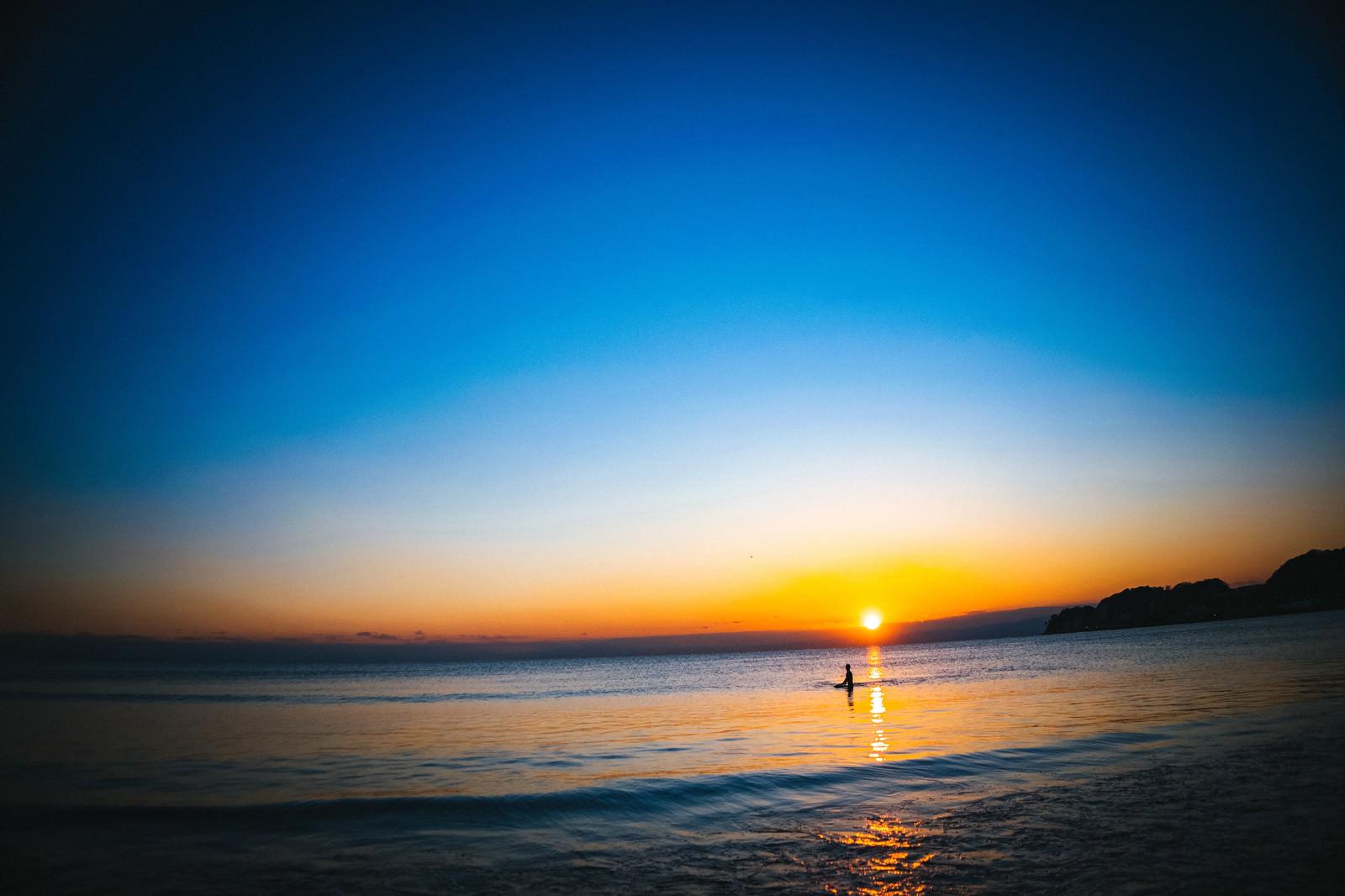 「夕日の焼けた海に浮かぶサーファー | 写真の無料素材・フリー素材 - ぱくたそ」の写真