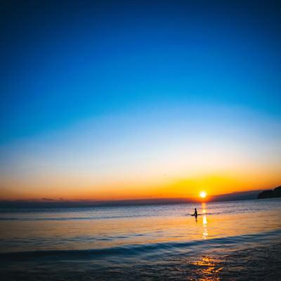 夕日の焼けた海に浮かぶサーファーの写真