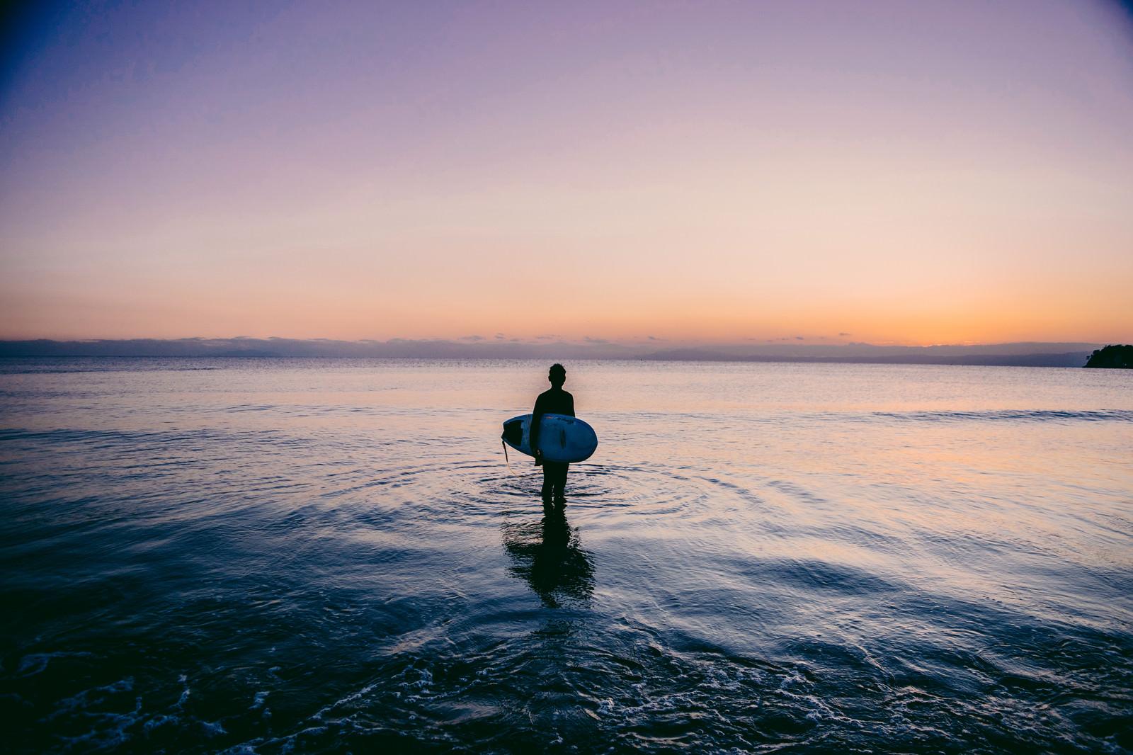 夕暮れの海に佇むサーファー 無料の写真素材はフリー素材のぱくたそ