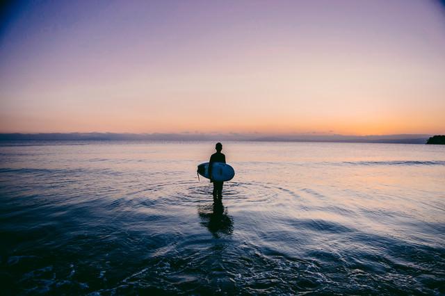 夕暮れの海に佇むサーファーの写真