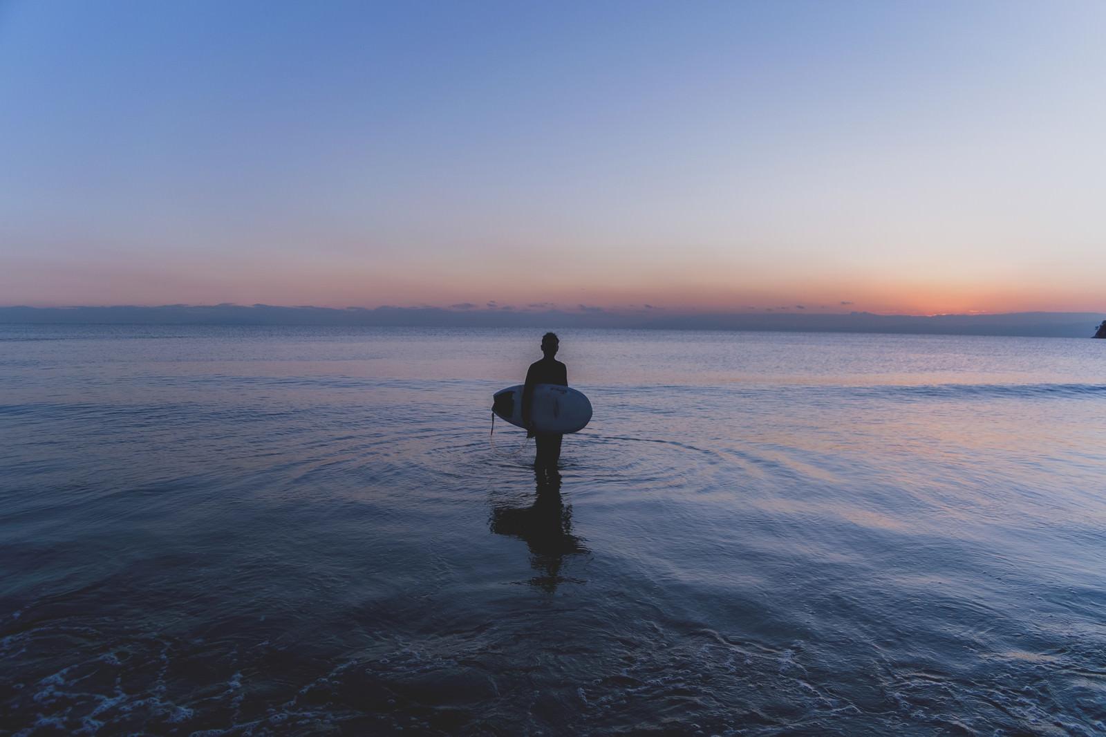 「日没の海に佇むサーファーの男性」の写真
