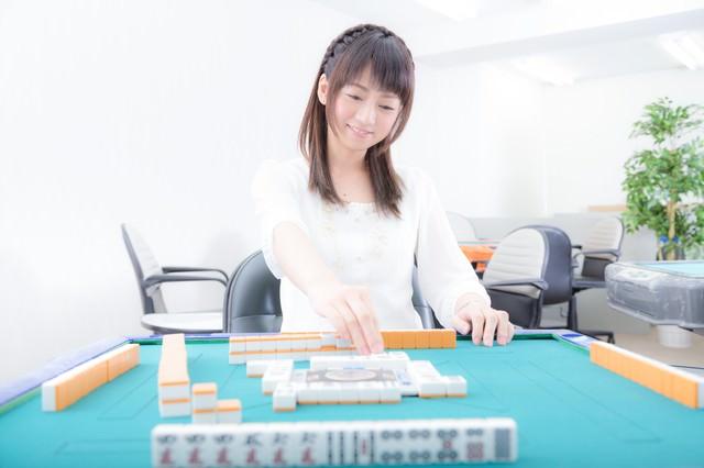「リーチ!」とかわいらしく打牌する女性の写真