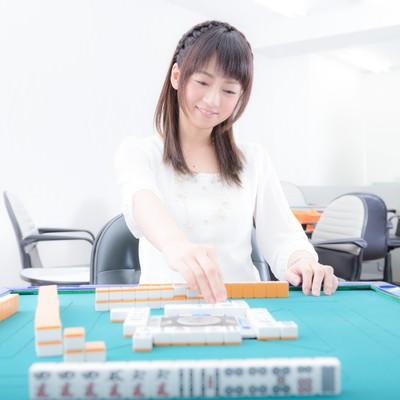 「「リーチ!」とかわいらしく打牌する女性」の写真素材