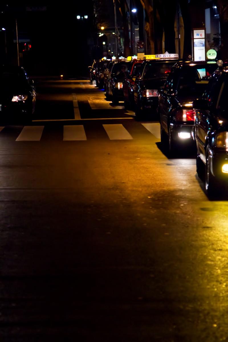 「客待ちで縦列する夜のタクシー」の写真