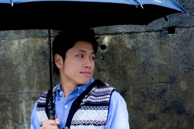傘を持ち振り返る男性の写真
