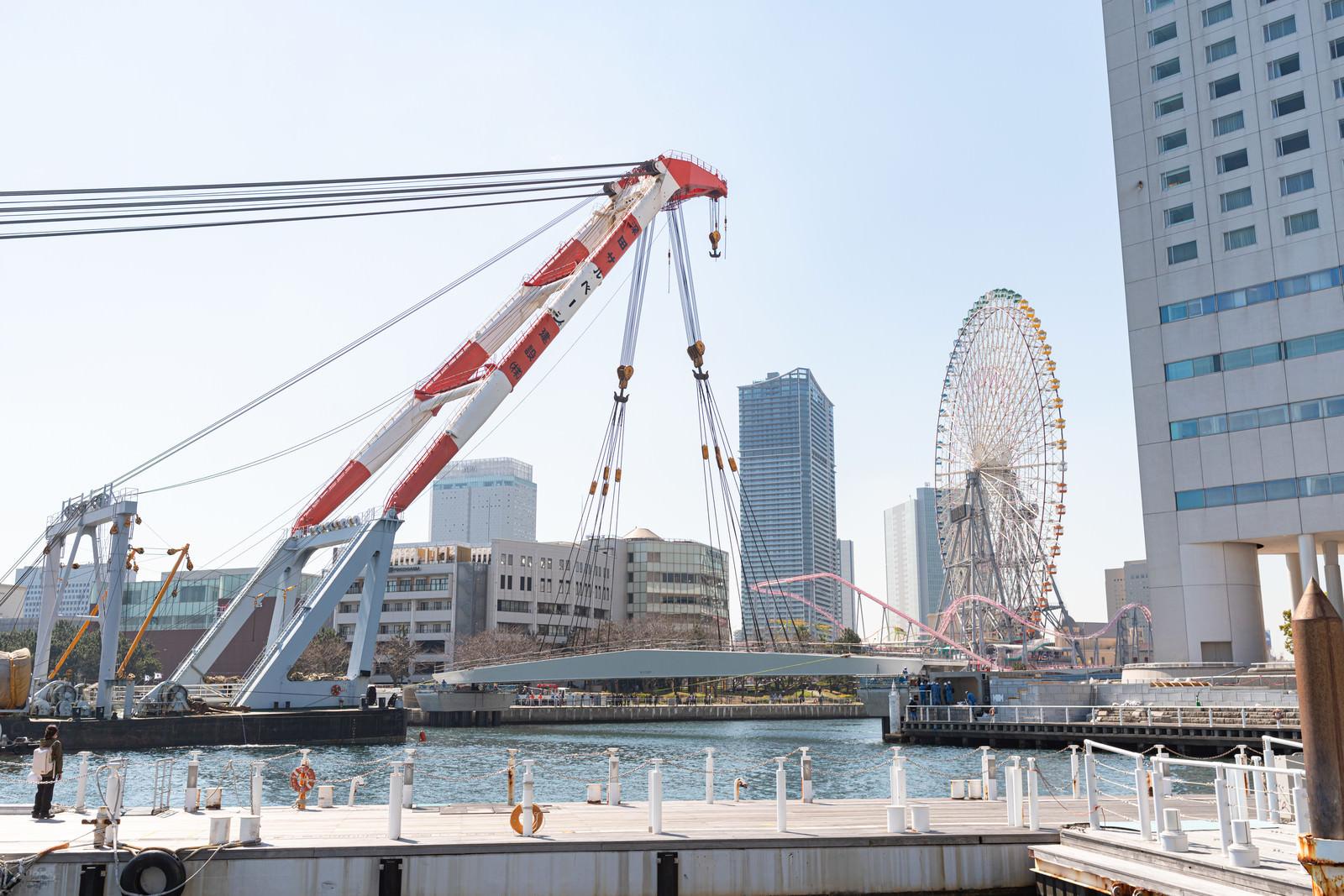 「MM21地区の新設デッキ「女神橋」をクレーンで吊るす様子」の写真