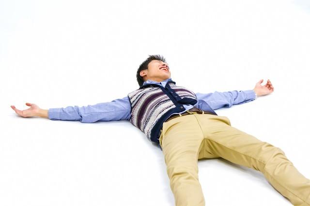 仰向けに寝て両手を広げる男性の写真